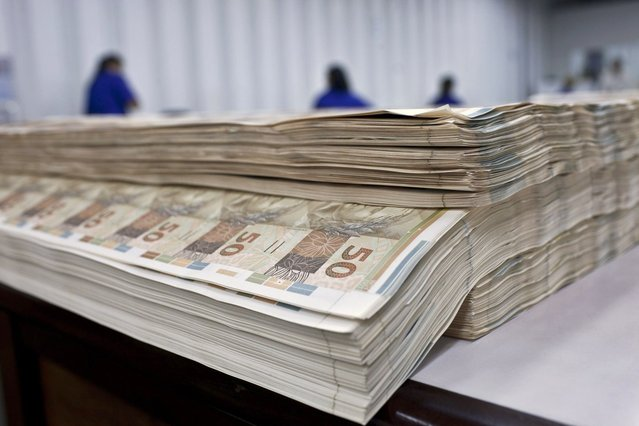 Prints of R$ 50 Brazilian reais bills sit on a table for inspection at at the Casa da Moeda, the national mint, in the Santa Cruz suburb of Rio de Janeiro, Brazil, on Tuesday, March 5, 2013. Brazil is likely to keep its key interest rate at a record low for the third straight meeting, as policy makers are caught between a fragile economic recovery and faster-than-expected inflation. (Photo by Dado Galdieri/Bloomberg)