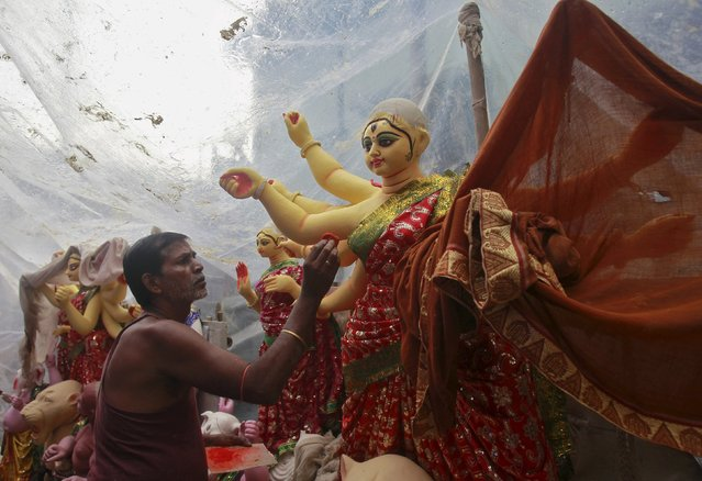 An artist paints an idol of the Hindu goddess Durga at a workshop ahead of the Durga Puja festival in Agartala, India, October 15, 2015. The Durga Puja festival will be celebrated from October 19 to 22, which is the biggest religious event for Bengali Hindus. Hindus believe that the goddess Durga symbolizes power and the triumph of good over evil. (Photo by Jayanta Dey/Reuters)