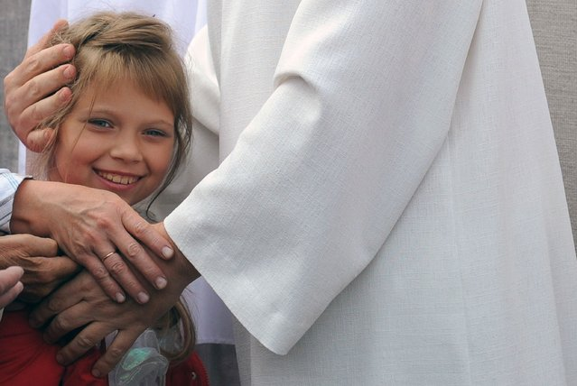"""""""Vissarion the Teacher"""", or """"Jesus of Siberia"""", Russian ex-traffic cop Sergei Torop hugs a small girl while meeting with his followers in the remote village of Petropavlovka on August 18, 2009. For thousands of followers, Vissarion is no less than the second coming of Jesus of Nazareth, reincarnated 2,000 years after his crucifixion, deep in the Siberian wilderness. (Photo by Alexander Nemenov/AFP Photo)"""