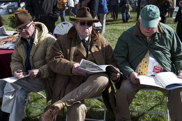 Men sit with their racing forms during the horse races at the Far Hills Race Day at Moorland Farms in Far Hills, New Jersey, October 17, 2015. (Photo by Stephanie Keith/Reuters)