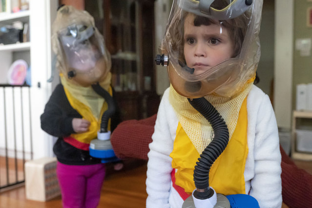 Buddy Mae Walker (R), 4, looks at herself in the mirror while trying on a child respirator provided by the non-profit TeamRaccoonPDX on October 6, 2020 in Portland, Oregon. (Photo by Nathan Howard/Getty Images)