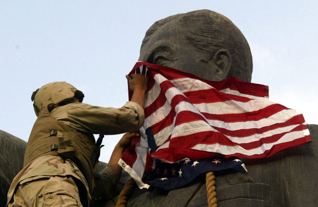 A U.S. Marine covers the face of a statue of Iraqi President Saddam Hussein with a U.S. flag in Baghdad, on April 9, 2003. U.S. troops briefly draped an American flag over the face of a giant statue of Hussein, as they prepared to topple it in front of a crowd of Iraqis. (Photo by Goran Tomasevic/Reuters/The Atlantic)