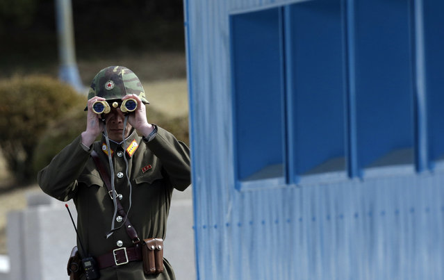 A North Korean soldier looks at the southern side through a pair of binoculars at the border village of the Panmunjom (DMZ) that separates the two Koreas since the Korean War, in Paju, north of Seoul, South Korea, Tuesday, March 19, 2013. The United States is flying nuclear-capable B-52 bombers on training missions over South Korea to highlight Washington's commitment to defend an ally amid rising tensions with North Korea, Pentagon officials said Monday. (Photo by Lee Jin-man/AP Photo)