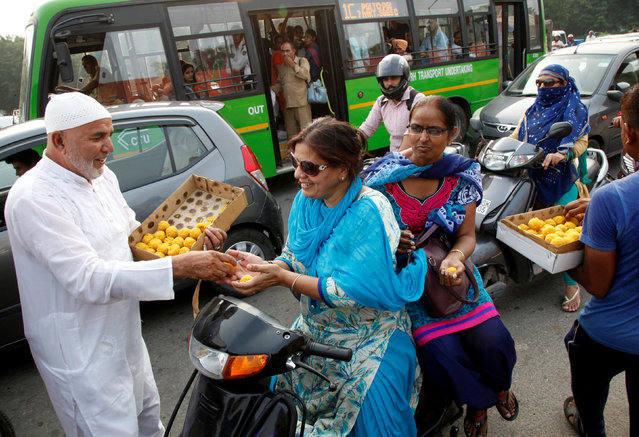 A man distributes sweets to commuters to celebrate after India on Thursday said it had conducted targeted strikes across the de facto frontier in Kashmir region, in Chandigarh, September 30, 2016. (Photo by Ajay Verma/Reuters)