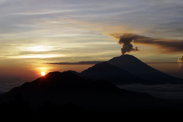 Mount Agung spews smoke at a sunrise in Kintamani, Bali, Indonesia, Wednesday, December 13 , 2017. Indonesia's disaster mitigation agency said the volcano remains at its highest alert level but most of Bali is safe for tourists. (Photo by Firdia Lisnawati/AP Photo)
