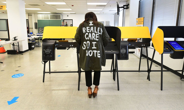 """Wearing a coat reading """"I Really Care So I Vote"""" written on the back, Tonya Swain votes in the 2020 US elections at the Los Angeles County Registrar in Norwalk, California on October 19, 2020. The coat is a reference to one worn by US First Lady Melania Trump which read """"I Really Don't Care Do You?"""". Voter turnout is ten times higher than in 2016 in California according the Secretary of State Alex Padilla as over 600,000 Los Angeles County ballots are already at the county registrar. (Photo by Frederic J. Brown/AFP Photo)"""