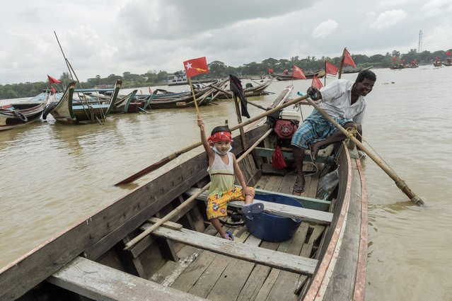 A child holds an emblem of the National League for Democracy (NLD) as supporters of ride on wooden boats in Yangon river, during an election campaign rally on the outskirts of Yangon on October 28, 2020, ahead of next month's elections. (Photo by Ye Aung Thu/AFP Photo)