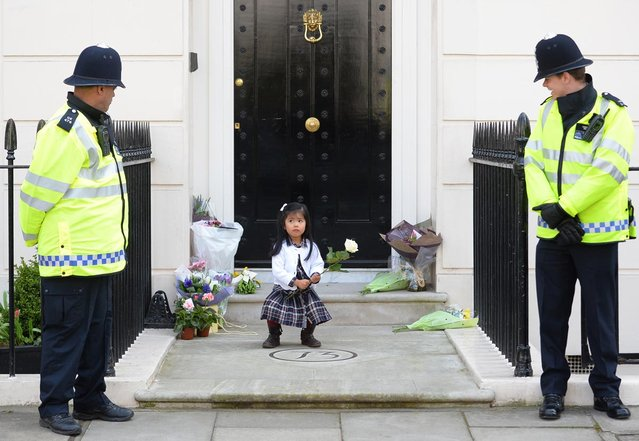 British police look on as a girl holds a rose amid floral tributes at the home of former British Prime Minister Margaret Thatcher in central London on April 10, 2013. British lawmakers will interrupt their holidays for a special session of parliament on April 10 to debate the legacy of Margaret Thatcher, who died on April 8 aged 87 after suffering a stroke. (Photo by Leon Neal/AFP Photo)