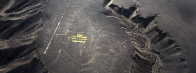 "Greenpeace activists stand next  to massive letters delivering the message ""Time for Change: The Future is Renewable"" next to the hummingbird geoglyph in Nazca in Peru, Monday, December 8, 2014. (Photo by Rodrigo Abd/AP Photo)"