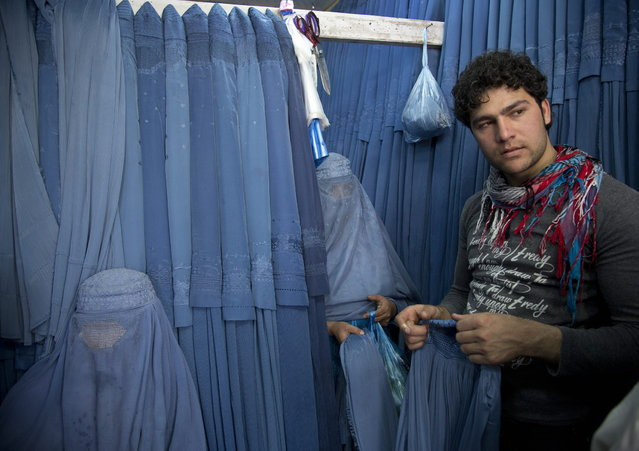 In this Thursday, April 11, 2013 photo, Nazar, right, a salesman at a burqa store, helps women to choose a burqa at a shop in the old town of Kabul, Afghanistan. (Photo by Anja Niedringhaus/AP Photo)