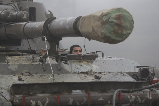 An Armenian soldier drives a self-propelled artillery unit during the withdrawal of Armenian troops from the separatist region of Nagorno-Karabakh, Wednesday, November 18, 2020. A Russia-brokered cease-fire to halt six weeks of fighting over Nagorno-Karabakh stipulated that Armenia turn over control of some areas it holds outside the separatist territory's borders to Azerbaijan. Armenians are forced to leave their homes before the region is handed over to control by Azerbaijani forces. (Photo by Sergei Grits/AP Photo)