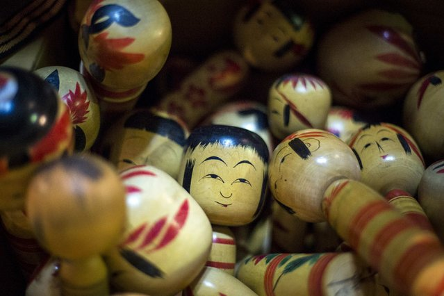 Traditional Kokeshi dolls from Japan's northern Tohoku area are piled up in a box at Boroichi flea market in Tokyo December 15, 2014. (Photo by Thomas Peter/Reuters)