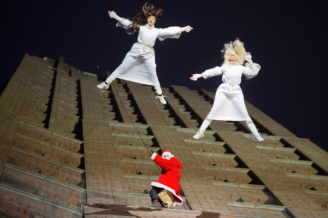 Climbers dressed as Santa Clause and two angels perform in an acrobatic dance show on December 14, 2014 in Berlin, Germany. The acrobatic dance show took place on the facade of the Kollhoff Tower, featuring performers abseiling down the 101 meters to the Potsdamer Platz. Gifts were given to children at the panoramic cafe on the 24th floor and at the bottom of the tower. (Photo by Target Presse Agentur Gmbh/Getty Images)