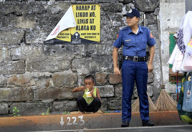 """A policeman stands in front of a boy eating noodles along a main street at Roxas Boulevard, metro Manila, November 9, 2015. The government has started moving out street dwellers living along a main street of metro Manila in preparation for the Asia-Pacific Economic Cooperation (APEC) summit meeting in Manila from November 18 to 19. The poster reads, """"My front side and back side, I clean and care"""". (Photo by Romeo Ranoco/Reuters)"""