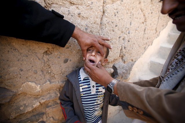 A boy is being held by relatives as he waits to receive polio vaccine drops during a house-to-house vaccination campaign in Yemen's capital Sanaa, November 10, 2015. (Photo by Khaled Abdullah/Reuters)