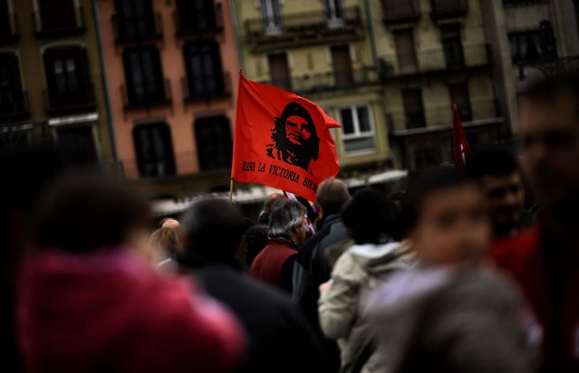 """A flag with the face of Che Guevara  reading, """"To the Victory. Always"""", waves during tMay Day celebrations in Pamplona, Spain. (Photo by Alvaro Barrientos/Associated Press)"""