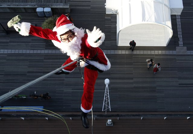 A window cleaner dressed as Santa Claus poses for pictures during an event to celebrate Christmas at a shopping mall in Tokyo December 24, 2014. (Photo by Yuya Shino/Reuters)