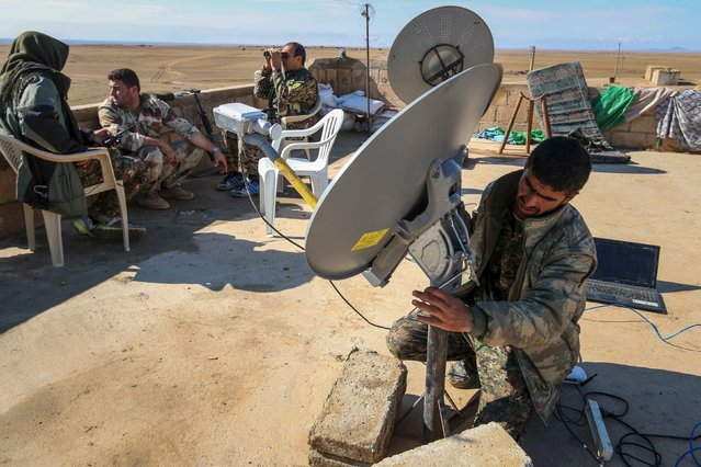 Rebel fighters form the Democratic Forces of Syria, sit on a rooftop as one of them fixes the direction of a satellite near al-Hawl area where fighting between them and Islamic State fighters are taking place in south-eastern city of Hasaka, Syria November 10, 2015. (Photo by Rodi Said/Reuters)
