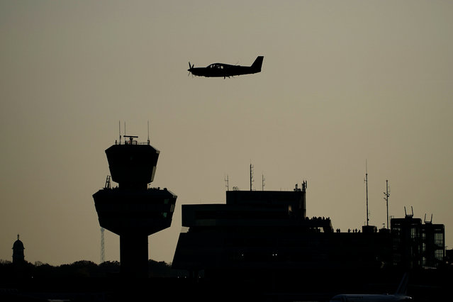 A sports aircraft flies past Tegel Tower, shortly before the last scheduled flight takes off from Berlin's Tegel Airport (TXL) in Berlin, Germany, Sunday, November 8, 2020. With the departure of the Air France aircraft AF 1235 to Paris at 15:00, Tegel Airport will close. (Photo by Michael Kappeler/dpa via AP Photo)