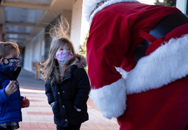 Dana Friedman, a trial lawyer who has spent 6 months of each year growing out his beard for his annual appearance as Santa Claus since 2001, greets children outside wearing masks as a precautionary measure at the Bay Terrace Shopping Center in Queens as the global outbreak of the coronavirus disease (COVID-19) continues, in New York City, U.S., December 6, 2020. (Photo by Caitlin Ochs/Reuters)