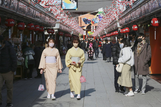 People wearing face masks to protect against the spread of the coronavirus walk under decorations for new year through the alley leading to Asakusa Sensoji Buddhist temple in Tokyo, Wednesday, December 16, 2020. Tokyo has reported 678 new cases of the coronavirus, a high for the Japanese capital, as Japan now struggles with another surge in the virus. (Photo by Koji Sasahara/AP Photo)