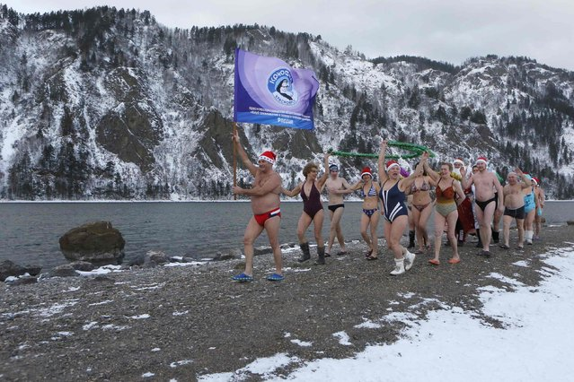 "Members of the ""Cryophil"" winter swimming club walk along the Yenisei River ahead of New Year and Christmas celebrations, with the air temperature at about minus 8 degrees Celsius (17.6 degrees Fahrenheit), outside Russia's Siberian city of Krasnoyarsk, December 28, 2014. (Photo by Ilya Naymushin/Reuters)"