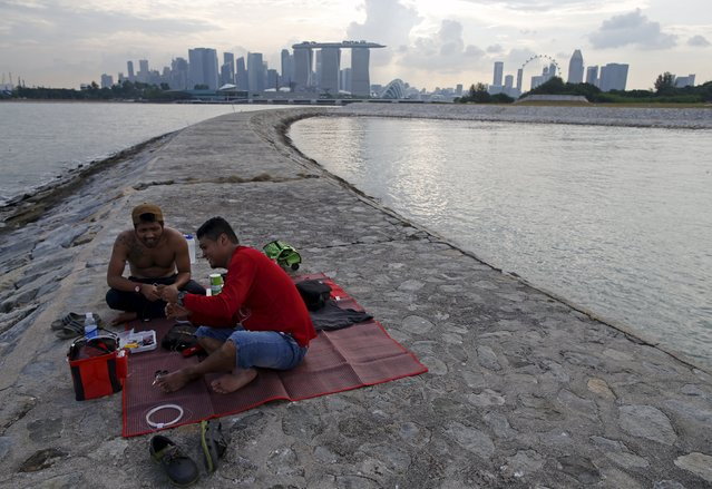 Men prepare their fishing lines on a breakwater, Singapore July 27, 2015. (Photo by Edgar Su/Reuters)