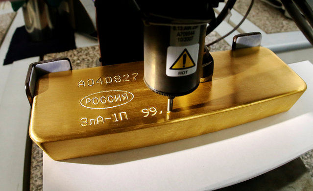 A machine engraves information on an ingot of 99.99 percent pure gold at the Krastsvetmet non-ferrous metals plant, one of the world's largest producers in the precious metals industry, in the Siberian city of Krasnoyarsk, Russia October 24, 2016. (Photo by Ilya Naymushin/Reuters)