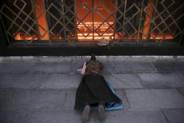 A Tibetan pilgrim prostrates herself at the Jokhang Temple in central Lhasa, Tibet Autonomous Region, China early November 20, 2015. (Photo by Damir Sagolj/Reuters)