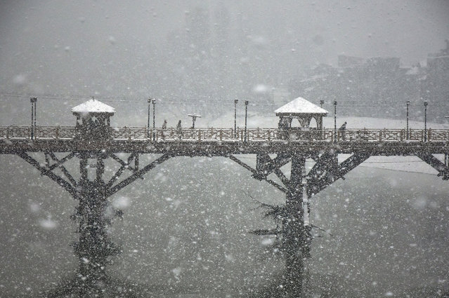 Commuters walk on a snow covered foot-bridge during heavy snowfall in Srinagar on January 4, 2021. Moderate to heavy snow continues for the second consecutive day in parts of Kashmir cutting the valley's surface as well as air connection with the rest of the world, officials said. The weatherman has forecasted widespread snowfall till the forenoon of December 6. (Photo by Saqib Majeed/SOPA Images/Rex Features/Shutterstock)