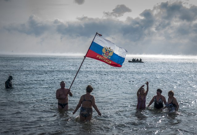 Crimean people wave a Russian national flag as they prepare to swim celebrating an Orthodox Christamas in the Black Sea with air temperature about –8 Celsius, (17.6 32 Fahrenheit) in Yevpatoria, Crimea, Wednesday, January 7, 2015. Orthodox Christians celebrate Christmas on Jan. 7, in accordance with the Julian calendar. A rescue boat patrols is in the background. (Photo by Alexander Polegenko/AP Photo)