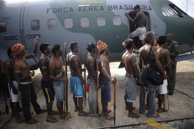 Munduruku Indians, many of who are flying for the first time, board a Brazilian Air Force plane to fly to Brasilia for talks with the government, in Altamira June 4, 2013. Air Force planes flew 144 Munduruku Indians to Brasilia for talks to end a week-long occupation of the controversial Belo Monte dam on the Xingu River, a huge project aimed at feeding Brazil's fast-growing demand for electricity. (Photo by Ueslei Marcelino/Reuters)