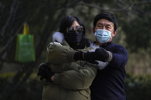 People wearing face masks to help curb the spread of the coronavirus, practice a social dance at a public park in Beijing, Tuesday, January 12, 2021. (Photo by Andy Wong/AP Photo)