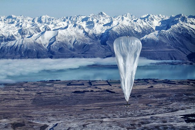 A Google balloon sails through the air with the Southern Alps mountains in the background, in Tekapo, New Zealand. (Photo by Jon Shenk/Associated Press)
