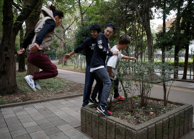 A parkour practitioner looks at Jun Sato (2nd L), founder of Japan's first parkour educational institute SENDAI X-TRAIN, plays with other practitioners  at a park in Tokyo, Japan November 2, 2016. (Photo by Kim Kyung-Hoon/Reuters)