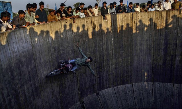 People watch as an acrobat rides his motorcycle around a circular track at an entertainment park set up outside a shrine in Rawalpindi, Pakistan, on June 19, 2013. (Photo by Muhammed Muheisen/Associated Press)