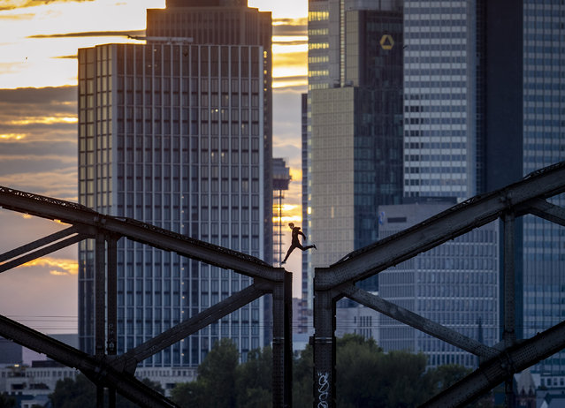 A parkour runner jumps on a railway bridge with the buildings of the banking district in background in Frankfurt, Germany, Wednesday, September 9, 2020. (Photo by Michael Probst/AP Photo)