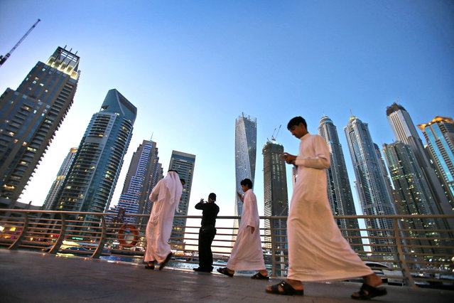 """In this April 1, 2015 photo, Gulf Arab visitors in their traditional """"Kandora"""" pass by giant skyscrapers at the Marina waterfront in Dubai, United Arab Emirates. The area is sometimes referred to as the Manhattan of the Middle East and some of its buildings are promoted by realtors as having """"Manhattan style"""" architecture. Penthouses in the Dubai Marina are similarly priced to New York City's upscale properties. (Photo by Kamran Jebreili/AP Photo)"""