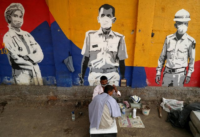 A roadside barber cuts the hair of a man in front of a wall with graffiti, amidst the spread of the coronavirus disease (COVID-19), in Mumbai, India, December 23, 2020. (Photo by Niharika Kulkarni/Reuters)