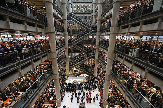 Workers and guests mark the two minute silence for Armistice Day in the Lloyd's Building on November 11, 2016 in London, England. People gathered at war memorials and in schools, offices and other public places across the UK paused for two minutes to commemorate the moment the guns fell silent for peace at the end of World War One, on 11 November 1918. (Photo by Leon Neal/Getty Images)