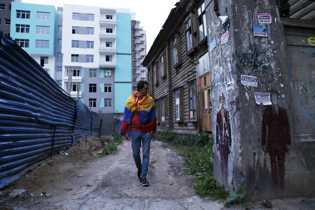In this Wednesday, June 20, 2018 filer, a soccer fan wrapped in a Colombian walks through an alley on the eve of the Group D match between Argentina and Croatia during the 2018 soccer World Cup n Nizhny Novgorod, Russia. (Photo by Ricardo Mazalan/AP Photo)