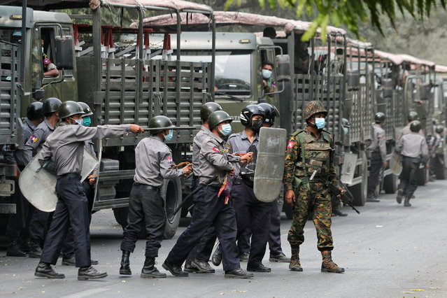 Police and soldiers are seen during a protests against the military coup, in Mandalay, Myanmar, February 20, 2021. (Photo by Reuters/Stringer)