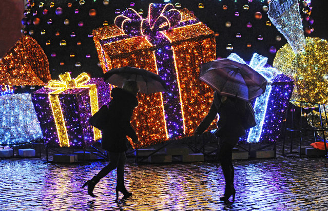 People walk past Seasonal decorations on a rainy evening in Warsaw, Poland, Tuesday, December 23, 2014, one day ahead of Christmas Eve. Weather forecasts predict a rainy Christmas in Poland. (Photo by Alik Keplicz/AP Photo)