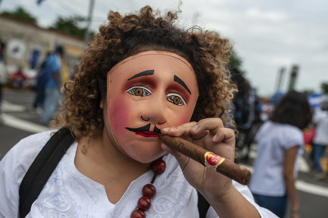 An anti-government demonstrator stikes a pose wearing a folklore mask and holding a cigar before the start of   march demanding the ouster of President Daniel Ortega and the release of political prisoners, in Managua, Nicaragua, Saturday, July 21, 2018. (Photo by Cristobal Venegas/AP Photo)