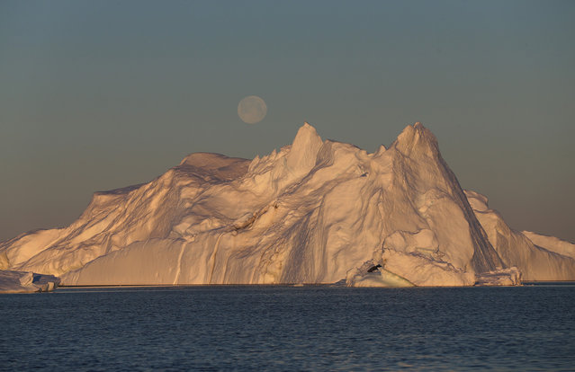 A full moon, over an iceberg from the Jakobshavn Glacier, on July 23, 2013 near Ilulissat. (Photo by Joe Raedle/Getty Images via The Atlantic)