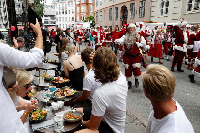 Diners react as a parade of people dressed as Santa Claus pass by during the World Santa Claus Congress, an annual event held every summer in Copenhagen, Denmark, July 23, 2018. (Photo by Andrew Kelly/Reuters)