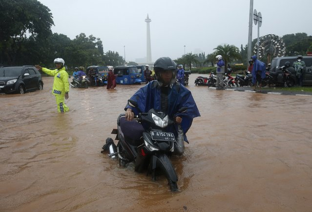 A motorcycle rider pushes his stalled bike on a flooded street outside the Presidential Palace, after heavy seasonal rains flooded parts of Jakarta February 9, 2015. (Photo by Darren Whiteside/Reuters)