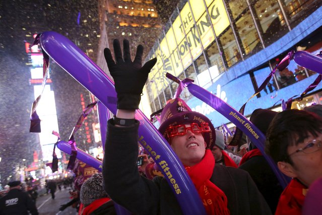 Revelers gather as confetti falls during New Year celebrations in Times Square in the Manhattan borough of New York December 31, 2015. (Photo by Andrew Kelly/Reuters)