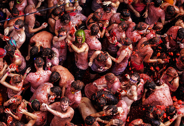 """Revellers battle with tomatoes during the annual """"Tomatina""""  in the Mediterranean village of Bunol, near Valencia, Spain. (Photo by Heino Kalis/Reuters)"""