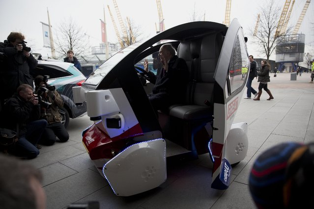Britain's Business Secretary Vince Cable holds his hands up as he poses for photographers in a prototype driverless car called a LUTZ (Low-carbon Urban Transport Zone) Pathfinder Pod during a launch event for the media near the O2 Arena in London, Wednesday, February 11, 2015. (Photo by Matt Dunham/AP Photo)